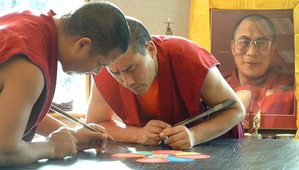 Two Tibetan monks working on Sand Mandala