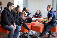 Students listening to an officer in a library