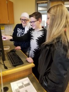 A reference librarian demonstrates a database for two students.