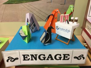 "origami penguins visit a student life table with popcorn and coffee near a sign reading ""Engage."""