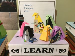 "origami penguins representing a variety of instruction departments near a sign reading ""Learn."""