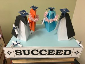 "origami penguins stand with graduation caps near a sign reading ""Succeed."""
