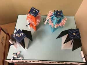"origami penguins in graduation caps that are decorated with ""2017"" and ""Thanks Mom!"" and bedazzled with jewels."
