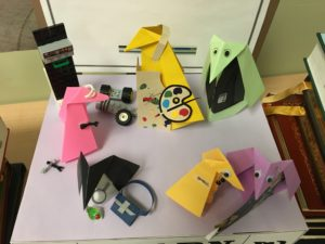 origami penguins in art smocks, working on robots and wearing business attire