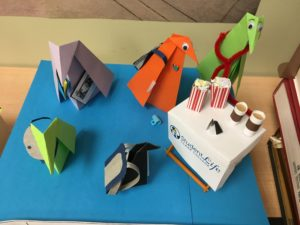 origami penguins with backpacks and messenger bags line up for coffee and popcorn
