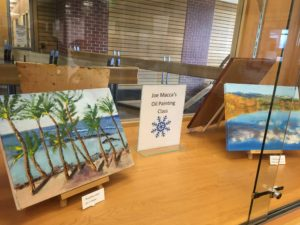 Two oil paintings of landscapes in a display case.