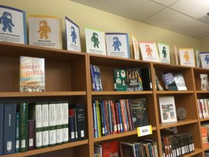 A row of books about women in science, math, and engineering, with small profiles of female astronauts.