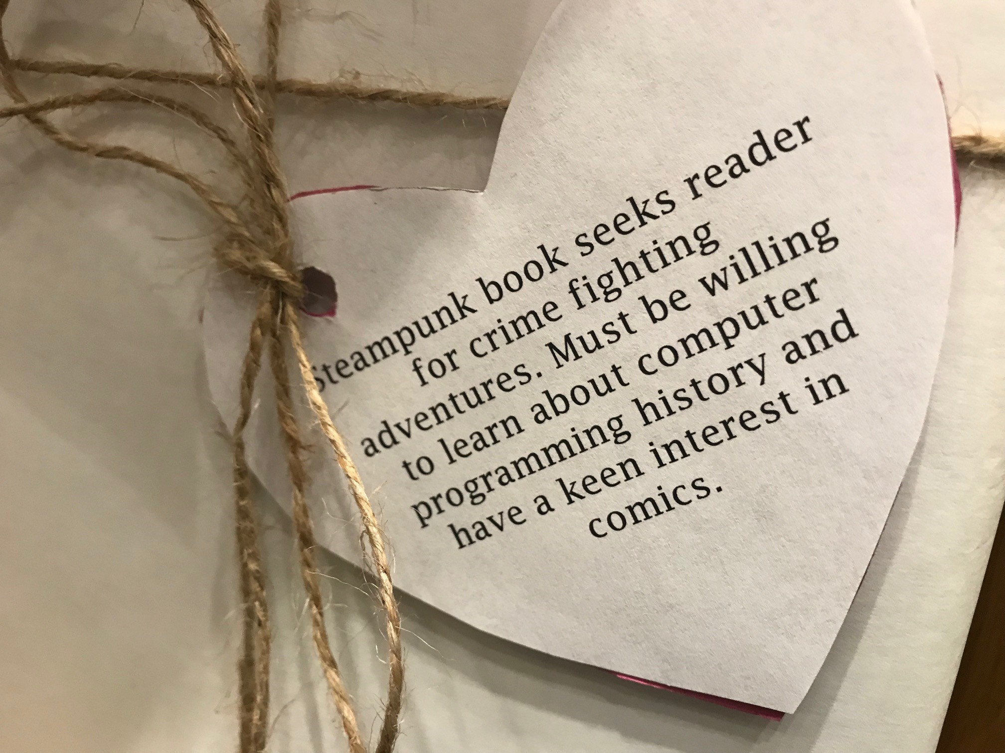 Heart tag attached to book says: Steampunk book seeks reader for crime fighting adventures. Must be willing to learn about computer programming history and have a keen interest in comics.
